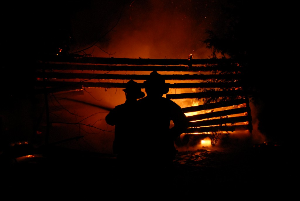 Firefighters from Edinburg Volunteer Fire Company hose down a blazing cabin at 1189 Edinburg Gap Road.