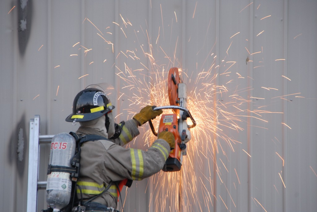 A firefighter uses a saw to cut open the wall to better reach the fire.