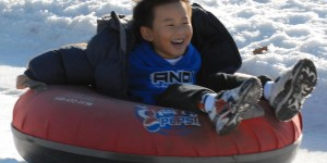 Boy snow tubing
